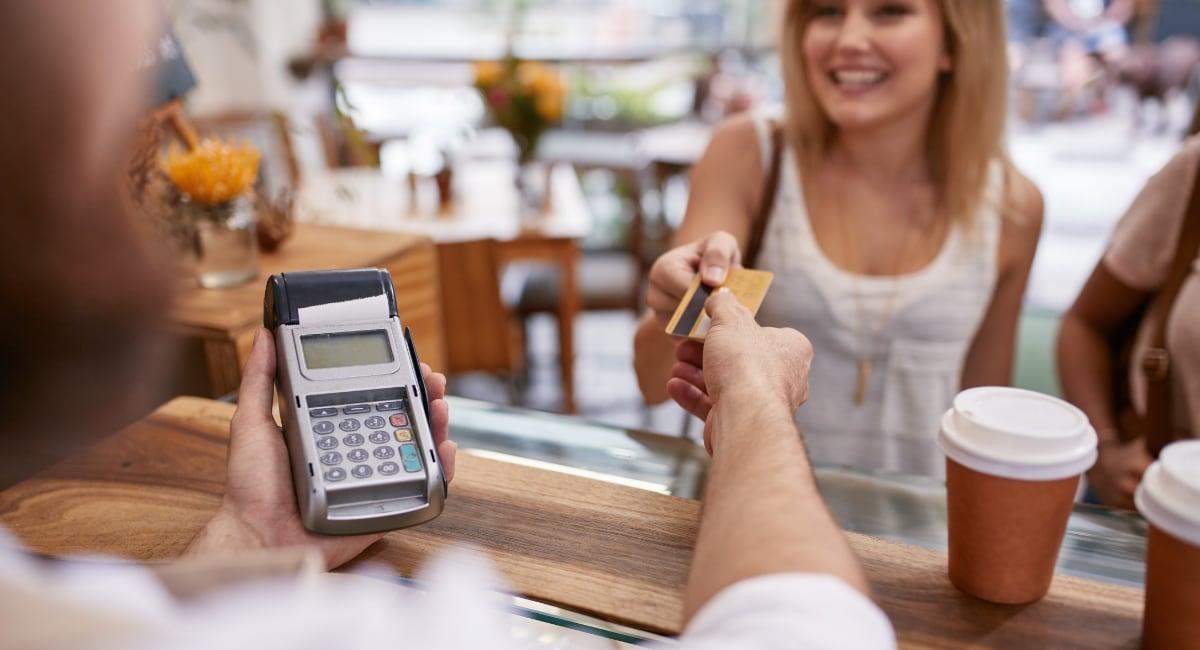 En kunde rækker et betalingskort over disken til en terminal