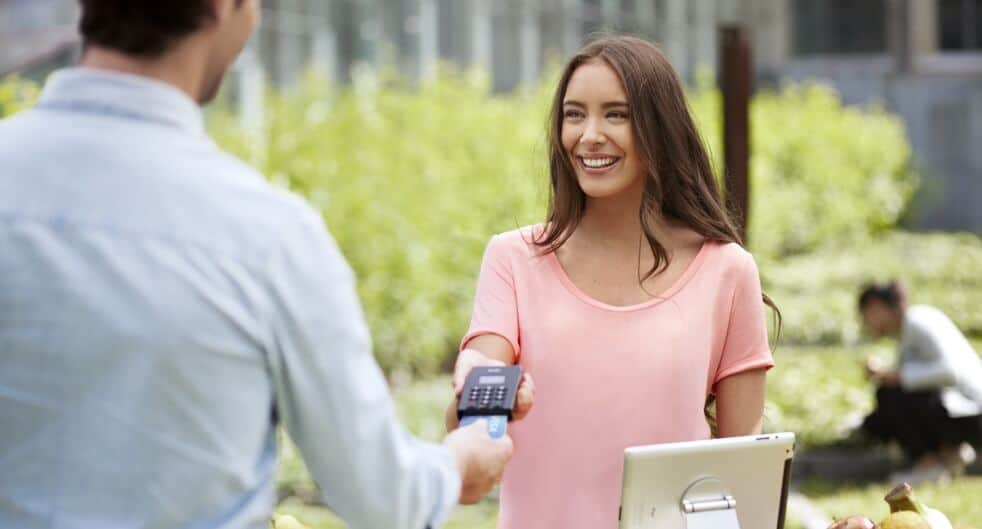 ekspedient der tager imod kort med mobil betalingsterminal