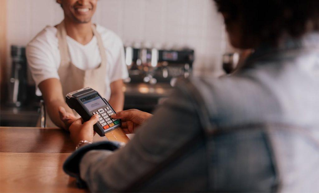 en kunde indtaster pinkode på en betalingsterminal