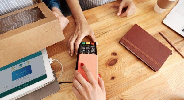 Hånd med mobiltelefon holdt over betalingsterminal på disk
